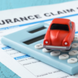 toy car on a calculator and insurance claim